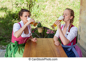 Drink Two women in Bavarian Dirndl with a beer