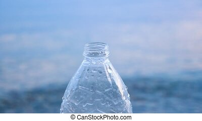 Drink water pouring into the bottle on seawater background. Safety water. Hygiene and sanitation background. Drops of water pouring into the bottle on seascape background. Drink and salt water