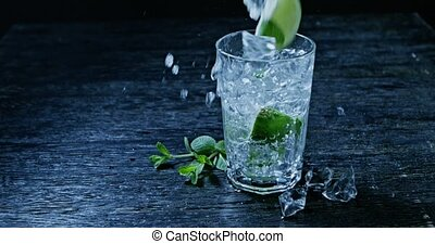 Drink with lime, mint and ice poured into a glass with splashes and spray. Slow motion 2k video shooted on 240 fps