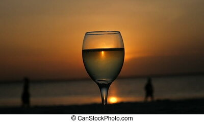 Drinking a glass of wine on the Indian Ocean with beautiful a beautiful sunset.