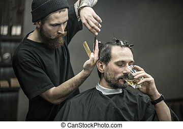 Drinking and cutting in barbershop - Brutal bearded man with...