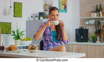 Cheerful housewife drinking aromatic tea at breakfast. Woman having a great morning drinking tasty natural herbal tea sitting in the kitchen smiling and holding teacup enjoying with pleasant memories.