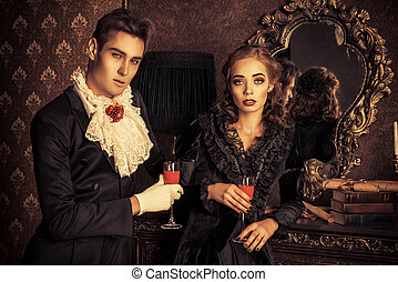 drinking blood - Beautiful man and woman vampires dressed in...