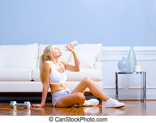 Side view of a young woman drinking bottled water after exercising. Horizontal shot.
