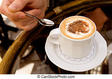 Drinking capuccino - Cup of cappuccino on a table in Krakow...