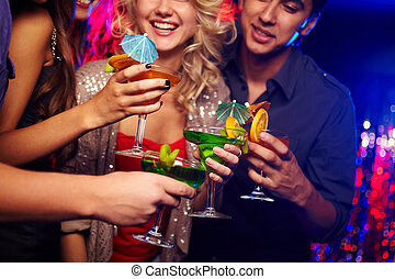 Drinking cocktails - Young people spending time in nightclub...