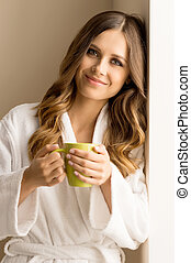 Drinking coffee at home. Beautiful young woman in bathrobe ...