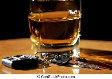 Drinking and driving photo of a glass of liquor sitting on a wood bar with a set of car keys in front of it (shallow focus).