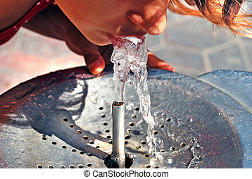 Girl drinking on water fountain outdoor close up