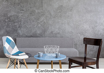 Ascetic coffee corner of a modern room, with blue coffee table and two designer chairs