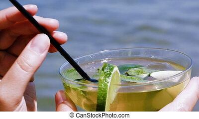 Drinking mojito with straw - Close-up shot of drinking...