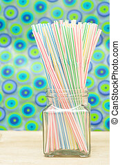 Drinking straws in a bottle with a colorful background