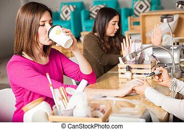Drinking tea at a nail salon