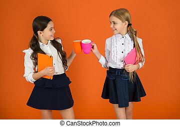 Drinking tea while break. School mates relaxing with drink. Enjoy being pupil. Girls kids school uniform orange background. Schoolgirl hold book or notepad and mug. School routine. Having break relax