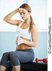 Drinking water after training. Beautiful young woman in sports clothing drinking water after training