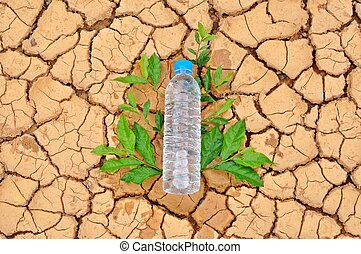 A water bottle on dry and cracked ground