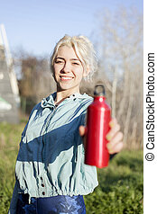 Drinking water concept. Female runner holding a red bottle