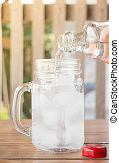 Drinking water is poured into iced glass, stock photo