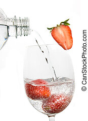 Drinking water poured over fresh strawberry fruit