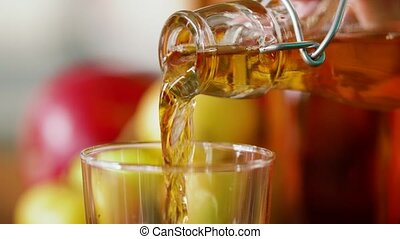 hand pouring apple juice from bottle to glass - drinks and...