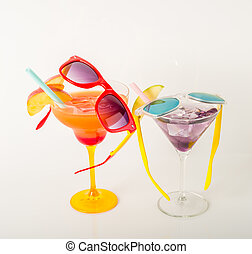 drinks decorated with fruit, margarita and martini glasses, drink straw and ice cubes