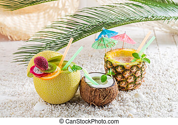 Drinks in fruits with cocktail umbrellas on white pebbles