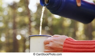 hands pouring tea from thermos to mug in forest - drinks, ...