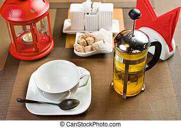 drinks - glass teapot with camomile-tea, on table in...