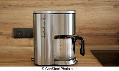 Drip coffee maker. Freshly brewed coffee is poured into a ...