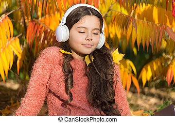 Drive by song. Enjoy music outdoors fall warm day. Audio file. Kid girl relaxing near autumn tree with modern wireless headphones. Music for autumn cozy mood. Listening songs. Melody for good mood