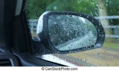 Drive in the rain View from inside the car, see the car's mirror. 4k, slow motion