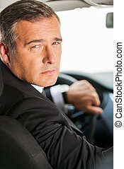 Drive responsible. Rear view of confident mature businessman driving car and looking over shoulder
