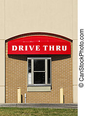 A window and drive thru sign on a brick building
