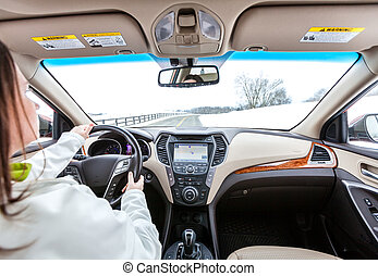Woman is driving a car. Interior view from the backseat