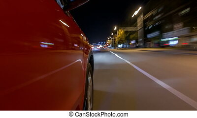 Drivelapse from side of car moving on a night avenue in city...