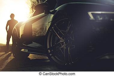 Driver and His Performance Car During Sunset