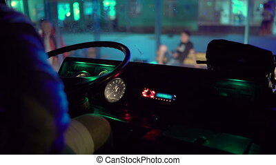 Driver behind the wheel of intercity coach leaves bus station terminal at night