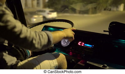 Driver behind the wheel of the bus riding on a city street at night