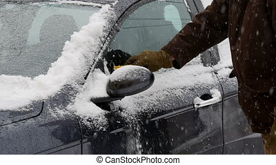 Driver cleaning snow  and entering to car