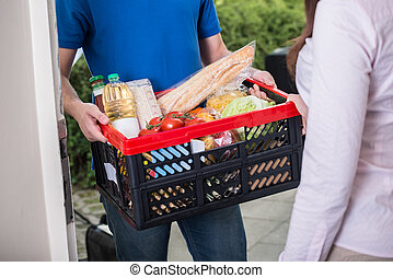 Close-up Of Man Delivers Crate Of Groceries At Home