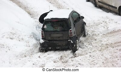 Driver digging out car stuck in snow. Bad weather conditions...