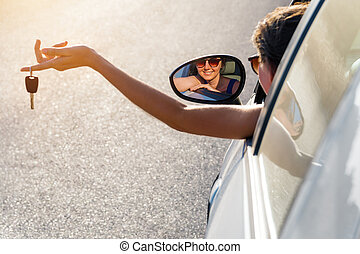 driver girl holds the keys to your car