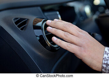 Driver hand on air ventilation grille with power regulator,...