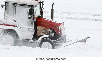 Driver on traktor clears road of snow in winter
