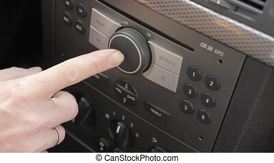 Driver presses button on a car audio system. hand adjusting...