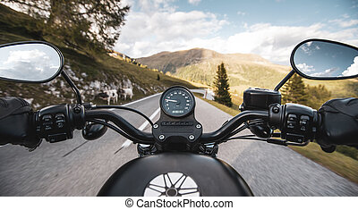 Driver riding motorcycle on an asphalt road in mountain, detail of steering bar.