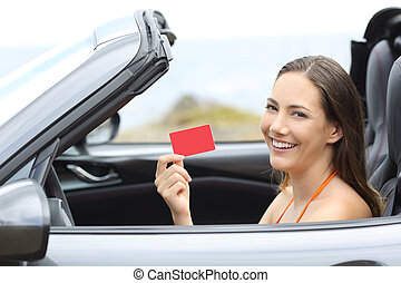 Driver showing a blank credit card in a cabriolet car