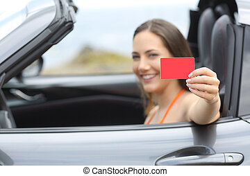 Driver showing a blank credit card in a car on vacation