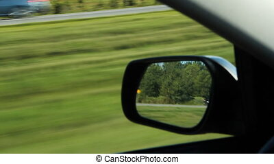 Driver side mirror. - Passing green grassy median....