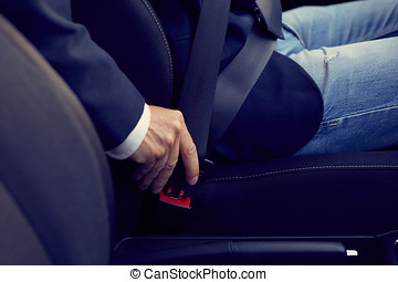Driver sits in the car and fastens his seat belt, toned